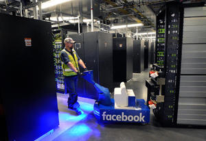 A logistics specialist uses a tug to move a server rack in one of the data halls at the newly opened Facebook data center in Los Lunas